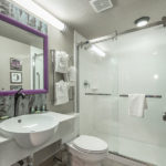 guest bathroom with toilet, standing shower, sink, and vanity at District 3 Hotel, An Ascend Hotel Collection Member