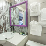 bathroom vanity with sink, mirror, and towels at District 3 Hotel, An Ascend Hotel Collection Member